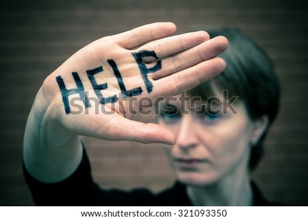 "A woman covers her face with his hand on his hand written in black marker ""help.""  #321093350"