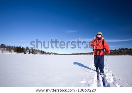 A woman cross country skiing across a frozen lake