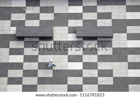 A woman crossing a black and white floor, from an overhead view #1116781823