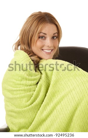 a woman cuddling up in a chair with her lime green blanket keeping her warm and cozy.