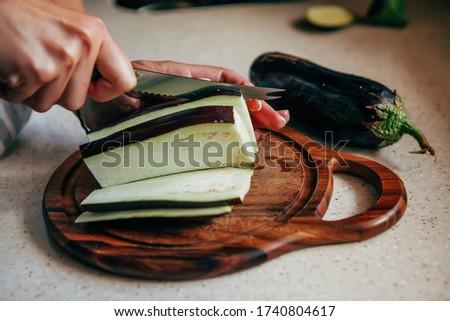 A woman cuts with a knife raw eggplant on a cutting board. Сток-фото ©