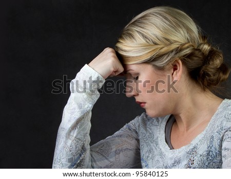 A woman deep in thought or with a headache, against a dark background room for copyspace