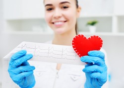 a woman doctor holds a red heart and a paper printout of a cardiogram. Prevention of cardiovascular diseases.