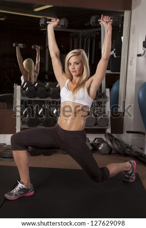 A woman doing a lunge with weights with a serious expression on her face.