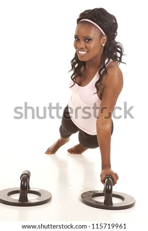 A woman doing a one arm push up with a smile on her face.
