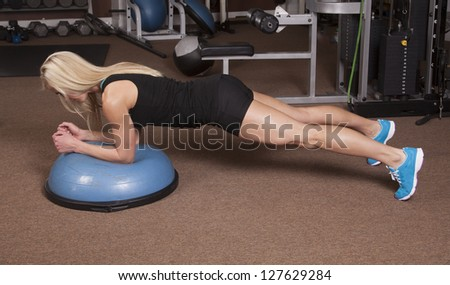 a woman doing a plank position in a gym.