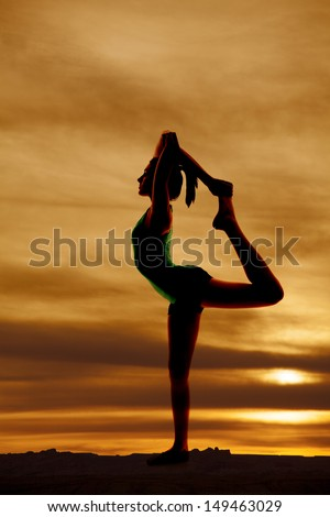 A woman doing a scorpion pose silhouette.