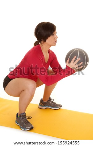 A woman doing a squat with her medicine ball with a serious expression on her face.