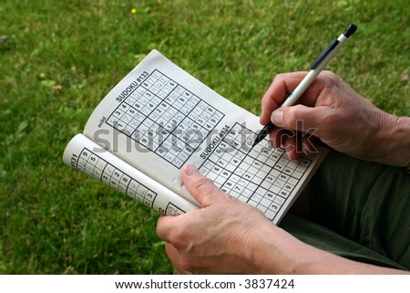 A woman doing a sudoku puzzle with pencil in hand