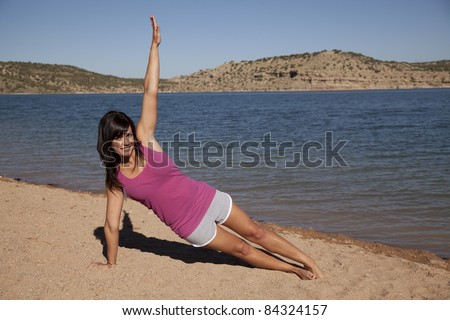 A woman doing her yoga stretch on the beach with a smile on her face.