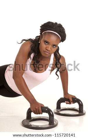 A woman doing push ups on bars with a serious expression on her face.