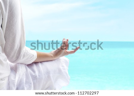 A woman doing yoga exercise with ocean view - stock photo