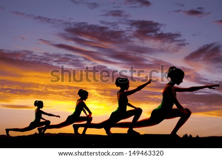 A woman doing yoga warrior pose silhouette.