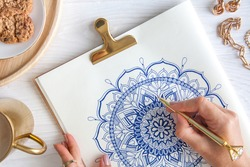 A woman draws a doodle mandala on a white sheet. Relax concept. White wooden table. Aged wood. A mug of coffee and chocolate chip cookies. Rosary and wooden beads.