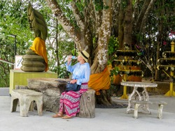A woman drinks water near sculpture of a seated Buddha