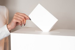 A woman drops a ballot into the ballot box. A woman votes in an election. The concept of elections. Voting in elections. The public referendum.