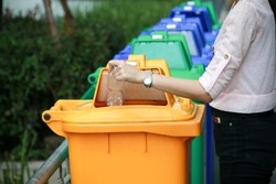 a woman dump a plastic bottle garbage to yellow recycle bin in a park