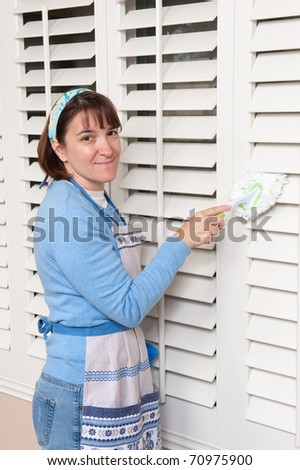 A woman dusts her window shutters while cleaning the house