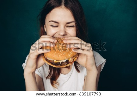 A woman eats with great pleasure, a woman eats a burger, food