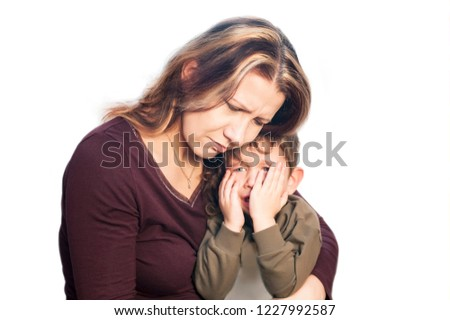 A woman embraces and soothes a boy who cries on a white background. The boy cries because his teeth are hurt. Isolated