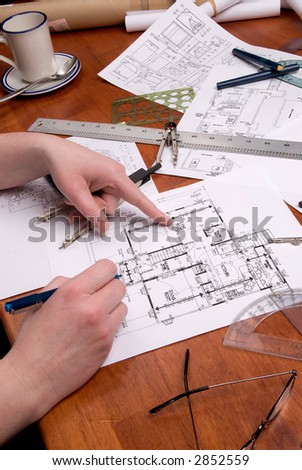 A woman engineer, architect or contractor working on and inspecting  blueprints or home plans