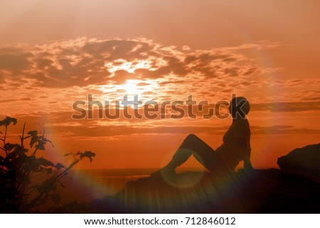 A woman enjoys the sunset and relaxes - enjoying in life #712846012