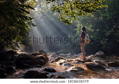A woman explores new, magical, and fantastic places around the world, surrounded by nature and spreading her arms to breathe and relax. Female hiker crossing the forest creek. stock photo