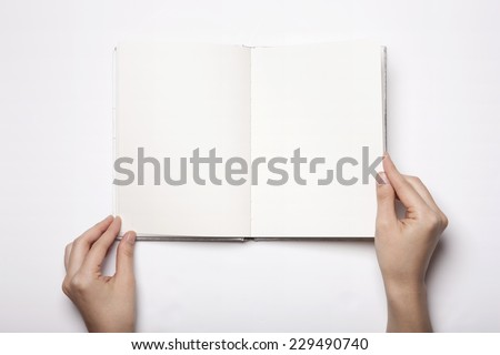 A woman(female) two hands hold a empty(blank) book(note, diary) spread(unfold) isolated white, top view, studio.