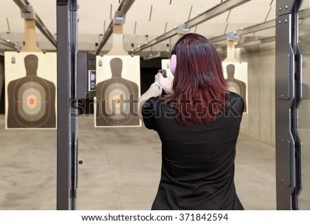 A woman firing a hand gun at an indoor gun range.