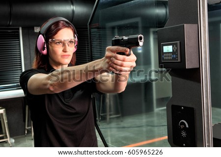a woman firing a hand gun at an ...