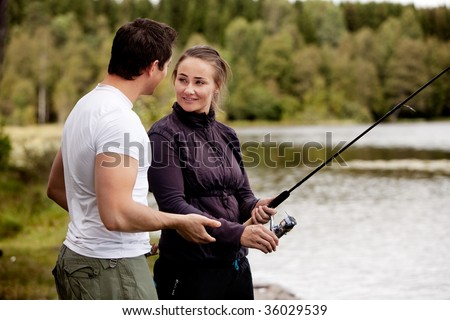 A woman fishing - showing a man
