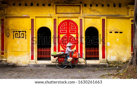 A woman fruit vendor in conical hat is waiting in front of a yellow and red old temple wall in central Hanoi, Vietnam.