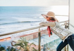 a woman gazes at the sea leaning on the railing of a hotel terrace.
