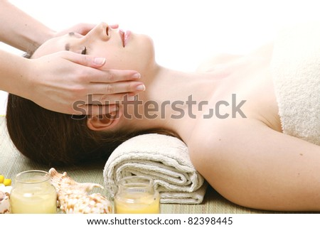 A woman getting a face massage, isolated on white