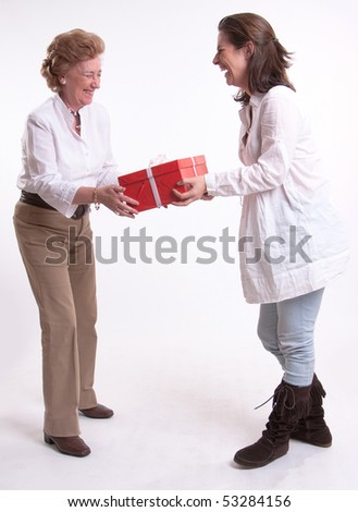 A woman giving a surprise gift to her mother