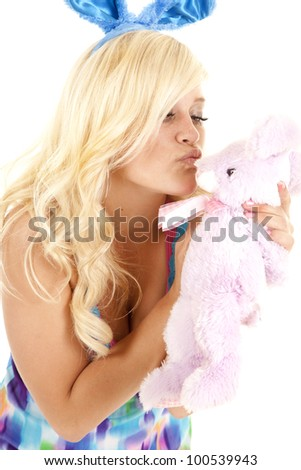A woman giving her stuffed bunny a kiss.