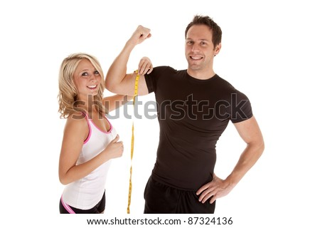 A woman giving her thumbs up at how big her man's muscles are.
