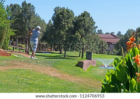 A woman golfer tees off on a sunny day in Arizona