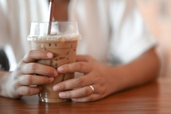A woman grabbing iced coffee with both hands in the coffee shop.