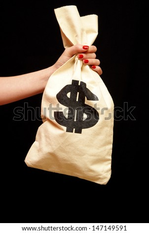 A woman grabs onto a large sum of cash in a bag.