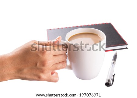 A woman hand holding a mug of coffee with creamer with a black notebook and a pen