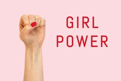 A woman hand on a pink background and inscription Girl power