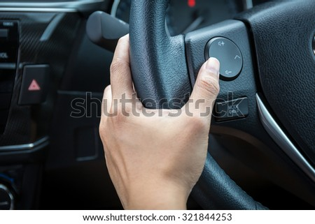 A woman hand pushes the volume control button on a steering wheel. #321844253