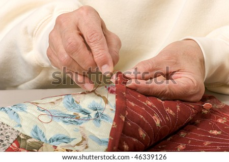 A woman hand sewing binding on a quilt.