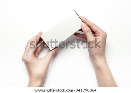 A woman hands hold a empty(blank, vacant, hollow) white paper box(package) for cosmetics, accessory, top view isolated white at the studio.
