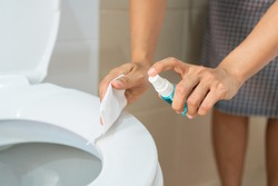 A woman hands with alcohol spray and wet wipe cleans a bathroom toilet before using. Protection against infectious virus, bacteria and germs, Coronavirus/ Covid-19, health care concept.