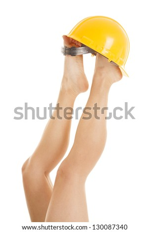 A woman has her legs up in the air with a construction hat on her feet. - stock photo
