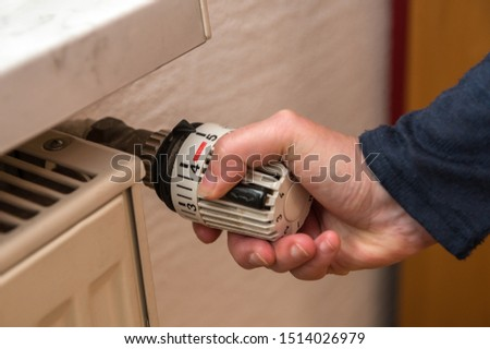 A woman has set a thermostat on a heater to a high value and wastes a lot of energy. Concept: heat or heating costs