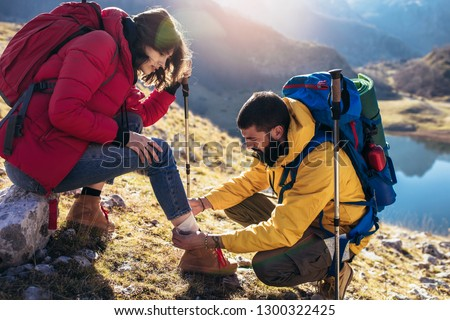 A woman has sprained her ankle while hiking, her friend uses the first aid kit to tend to the injury #1300322425