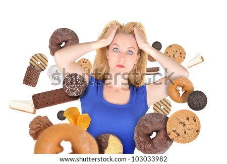 A woman has sweet food snacks around her on a white background. She has fear and there are donuts and cookies. Use it for a health or diet concept.